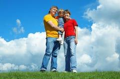Soporte feliz de la familia en hierba verde bajo el cielo fotografía de archivo libre de regalías