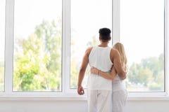 Soporte hermoso joven de los pares cerca del abrazo grande de la ventana, del hombre de la sonrisa feliz y del abrazo hispánicos  imagen de archivo