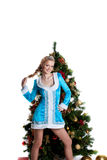 Soporte joven de la muchacha de la Navidad con el árbol de abeto del Año Nuevo Imágenes de archivo libres de regalías