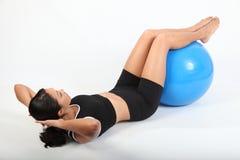 Soporte los crujidos por la mujer del ajuste que usa la bola del ejercicio Fotos de archivo libres de regalías
