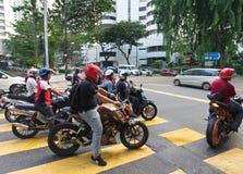 Soporte malasio de los motoristas en los semáforos Imagenes de archivo