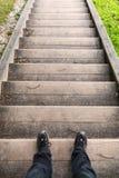 Soporte masculino de las piernas en las escaleras de madera viejas Imágenes de archivo libres de regalías