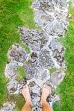 Soporte masculino de las piernas en un camino rocoso Imagen de archivo libre de regalías