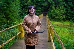 Soporte mayor feliz de la mujer en el puente de madera hecho a mano en el centro del bosque imagen de archivo libre de regalías