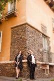 Soporte mayor feliz de los pares en crecimiento completo cerca de la pared de la casa en el verano Capa y paraguas-bastón de cuer fotos de archivo libres de regalías