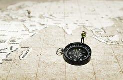 Soporte minúsculo del modelo del viajero en el compás sobre mapa marrón Fotografía de archivo