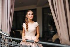 Soporte moreno elegante de la señora en balcón de lujo y sonrisa Peinado y maquillaje de la moda imágenes de archivo libres de regalías