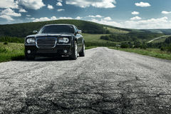 Soporte negro de Chrysler 300c del coche en la carretera de asfalto en el d3ia Imagenes de archivo