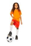 Soporte negro lindo de la muchacha en balón de fútbol en estudio Fotos de archivo
