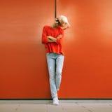 Soporte rubio elegante cerca de la pared roja en la calle de la ciudad Fotografía de archivo