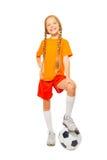 Soporte rubio lindo de la muchacha en balón de fútbol en estudio Fotografía de archivo
