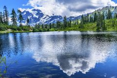 Soporte Shuksan Washingt de la reflexión de las nubes de los árboles de hoja perenne del lago picture Foto de archivo