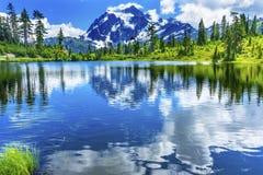 Soporte Shuksan Washingt de la reflexión de las nubes de los árboles de hoja perenne del lago picture Imagen de archivo