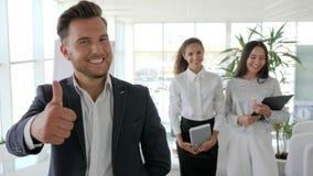 Soporte sonriente del mentor con los oficinistas en el centro de negocios, ejecutivo que da los pulgares para arriba en el equipo almacen de metraje de vídeo