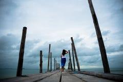 Soporte triste y solo de la mujer solamente en el puente de madera imagen de archivo libre de regalías