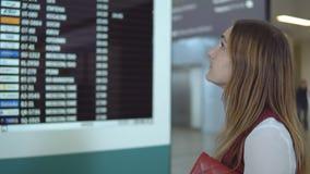 Soportes caucásicos hermosos de la muchacha y vuelo bien escogido en el fondo del marcador borroso con el aviso almacen de metraje de vídeo