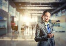 Soportes de la mujer de negocios que miran su teléfono Foto de archivo libre de regalías