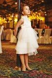 Soportes de la niña que la inclinan detrás en el lamppost Fotos de archivo