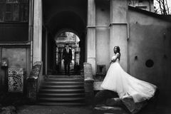Soportes de la novia en las piedras que separan vestido mientras que camina el novio Imagen de archivo libre de regalías