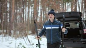Soportes del hombre con los esquís cerca del coche en el bosque del invierno