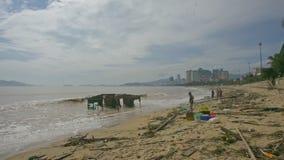 Soportes del hombre en casa arruinada relojes de la playa después del huracán