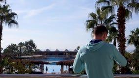 Soportes del hombre en el mar y las palmeras de desatención de la terraza almacen de metraje de vídeo