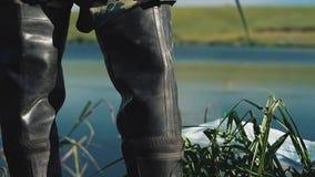 Soportes del pescador en botas y pescados de las capturas almacen de video