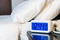 Soportes electrónicos del despertador en una mesita de noche cerca de la cama Foto de archivo libre de regalías