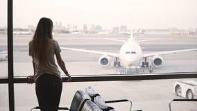 Soportes europeos jovenes de la empresaria que miran de ventana del salón del terminal de aeropuerto, de miradas y del reloj eleg almacen de video