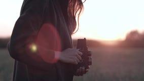 Soportes femeninos en campo con la cámara del vintage, en puesta del sol del fondo con resplandor del sol almacen de video