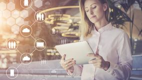 Soportes jovenes y aplicaciones de la empresaria digitales En primero plano son los iconos virtuales con las nubes, gente, artilu Foto de archivo libre de regalías