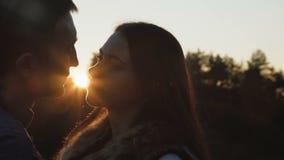 Soportes preciosos de los pares en suavemente abrazos y besos en puesta del sol 4K almacen de metraje de vídeo
