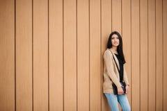Soportes sonrientes de la mujer hermosa elegante cerca de una pared de madera Imagen de archivo libre de regalías