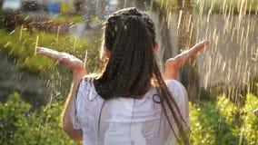 Soportes sonrientes jovenes de la mujer debajo de la lluvia fresca en verano Ella se divierte mucho que pasa sus días de fiesta e metrajes