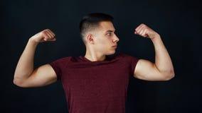 Soportes y actitudes del hombre joven Él muestra los músculos en las manos y las besa Aislado en fondo negro almacen de metraje de vídeo