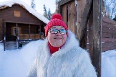Soportes y sonrisas alegres de la mujer feliz en la entrada de la casa de madera del pueblo fotos de archivo libres de regalías