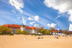 Sopot Baltic beach. People relaxing on beach on the second plane beautiful architecture of Sopot, on May 03, 2016 in Sopot, Poland Stock Images