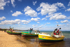 Sopot beach. Old fishing boats on the coast in the background people walk on beach, on May 02, 2015 in Sopot, Poland Royalty Free Stock Photography