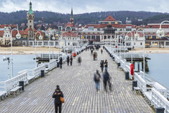 Sopot Pier Molo in the city of Sopot, Poland. People walking on a pier Molo in Sopot city, Poland. Built in 1827 with 511m long it is the longest wooden pier in royalty free stock image