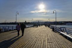 The wooden pier on September 30, 2017 in Sopot, Poland. SOPOT, POLAND: SEPTEMBER 30, 2017: Tourists walking on the wooden pier on September 30, 2017 in Sopot royalty free stock photography