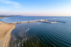 Wooden pier with marina and yachts in Sopot resort, Poland. Sopot resort in Poland. Wooden pier molo with marina, yachts, pirate tourist ship and beach, Far Stock Image