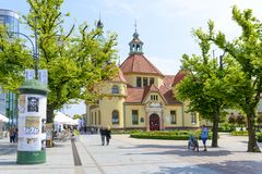 Sopot street. Tourists enjoy the sunny weather and walking in front of the balneological clinic with a lighthouse on 26 May 2018 in Sopot, Poland. The building royalty free stock photo