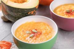Soppa för puré för höstpumpa i keramiska koppar på en grå textural bakgrund arkivbilder