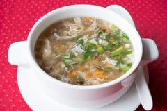 Soppa för traditionell kines med nötkött och västra sjönötkött för grönsaker i en vit platta på en röd bakgrund Royaltyfria Foton