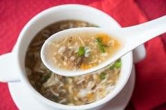 Soppa för traditionell kines med nötkött och västra sjönötkött för grönsaker i en vit sked på bakgrunden av en platta Top beskåda Royaltyfri Fotografi