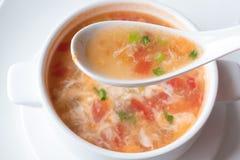Soppa för traditionell kines med tomater och ägget i en vit sked på bakgrunden av en platta Top beskådar Arkivbilder