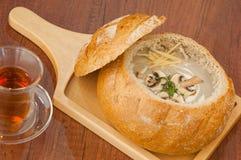 Soppa i en brödbunke på brädet royaltyfria bilder