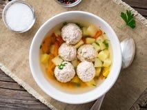soppa med köttbullar i den vita plattan på den gamla trälantliga grå färgtabellen, bästa sikt arkivbild