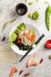 Soppa med skaldjur, nudlar och grönsaker i en vit platta Royaltyfri Foto