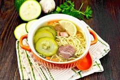 Soppa med zucchinin och nudlar i bunke på mörkt bräde Royaltyfri Bild